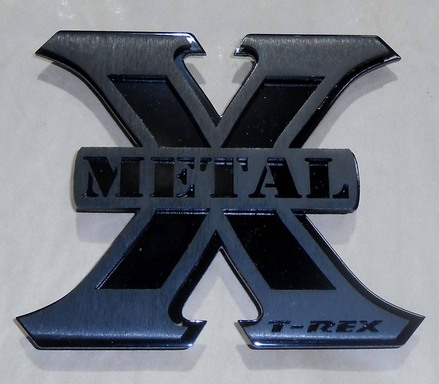 T-REX Grilles - Medium X-Metal Logo, 4 1/4 Inch Height x 5 Inch Wide, Black Anodized Front Plate with Gloss Black Back Plate